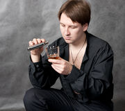 Sad young man pouring whiskey. From steel flask Stock Photo