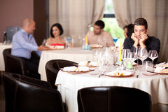 Sad young man at restaurant table Stock Image