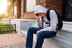 Sad Young Man. In a Hoodie sit on the City Street Stock Photo
