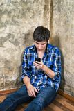 Sad Young Man. With a Phone on the Floor by the Old Wall Royalty Free Stock Photography