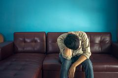 Sad man  sitting on sofa in dark room. Sad young man in shirt sitting on sofa and right Royalty Free Stock Photography