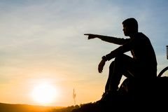 Sad young man silhouette worried on the stone. At sunset ,Silhouette concept Stock Photography