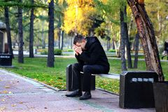 Sad Young Man. Sad Man sit on the Bench in the Autumn Park royalty free stock photo