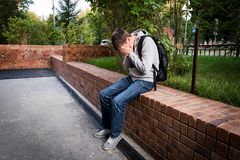 Sad Young Man. Sit on the City Street Royalty Free Stock Images
