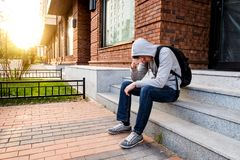 Sad Young Man. Sit on the City Street royalty free stock photo