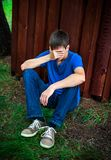 Sad Young Man outdoor. Sad Young Man sit on the Ground by the Wall Royalty Free Stock Photography