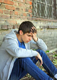 Sad Young Man. Sit near the Brick Wall of the Old House Stock Image