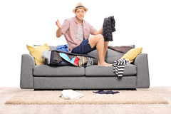 Sad young man sitting on his overstuffed suitcase Royalty Free Stock Images