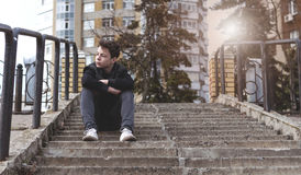 Sad young man sitting on the stairs. Sad, pensive young man sitting on the stairs Stock Image