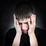 Sad Young Man. Sorrowful Young Man on the Black Background Royalty Free Stock Image