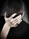 Sad Young Man. Sorrowful Young Man on the Black Background Royalty Free Stock Images