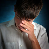 Sad Young Man. Sorrowful Young Man on the Dark Background royalty free stock images