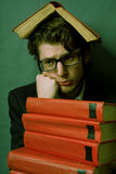 Sad young man with a stack of red books Stock Images