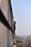 Sad young man standing on the edge of a bridge. Looking away thi Royalty Free Stock Photography