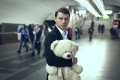 Sad young man in a subway station. He holds a toy bear in his hands stock photography
