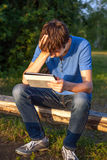 Sad Young Man with Tablet. Computer on the Wooden Bench Stock Photo