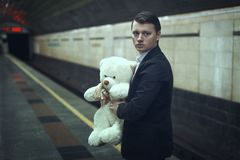 Sad young man with a teddy bear. Sad young man with a teddy bear in his hands is standing at a subway station stock images