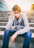 Sad Young Man. Toned Photo of Sad Young Man sit on the City Street royalty free stock photos