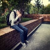 Sad Young Man. Toned Photo of Sad Young Man sit on the City Street stock image