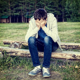 Sad Young Man. Toned Photo of Sad Young Man sit on the Log outdoor Stock Photo