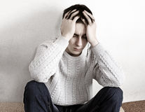 Sad Young Man. Toned Photo of Sad Young Man sit on the Sofa at the Home Stock Photos