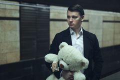 Sad young man is waiting for his beloved. Sad young guy holds a stuffed toy and waits for a lover stock photo