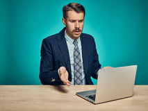 Sad Young Man Working On Laptop At Desk Stock Photo