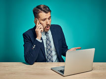Sad Young Man Working On Laptop At Desk Royalty Free Stock Photography