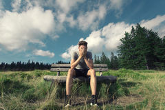 Sad young men on wooden bench Stock Photos