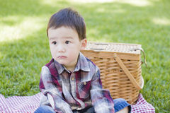 Sad Young Mixed Race Boy Sitting in Park Near Picnic Basket Stock Images