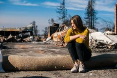 Woman at burned ruined house and yard, after fire disaster royalty free stock image