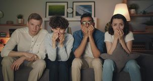 Sad young people watching tv at night crying wiping faces with paper tissues stock video footage