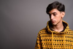 Sad young Persian teenage boy thinking against gray background royalty free stock image