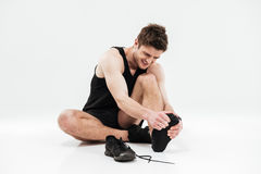 Sad young sportsman sitting isolated have a painful feelings. Stock Photography