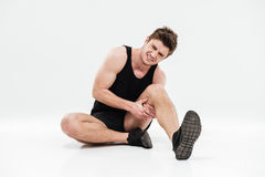 Sad young sportsman sitting isolated have a painful feelings. Royalty Free Stock Photo