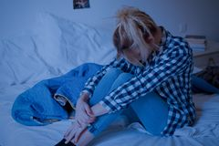 Sad young victim girl and suffering depression. Sad young victim girl sitting on the bed at home suffering depression royalty free stock photography