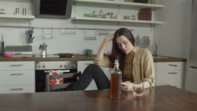Woman waiting for call drinking alcohol in kitchen stock video footage