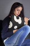 Sad young woman. Young woman in pain curled up on sofa Stock Images