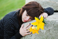 Sad young woman lying on tombstone Royalty Free Stock Images