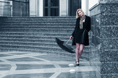 Sad young fashion woman with umbrella at the wall Stock Images