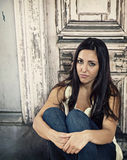Sad young woman. Sad, worried young woman sitting and holding her knees in front of an old weathered door.. Troubled stock photos