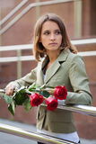 Sad young fashion woman with a red roses outdoor Royalty Free Stock Images