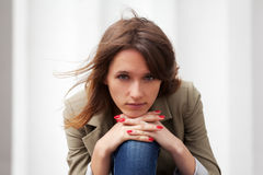Sad young fashion woman. Against a white wall royalty free stock photo