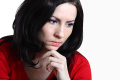 Sad young woman. Good looking brunette with long hair sitting supporting her head with hand looking depressed Stock Photo