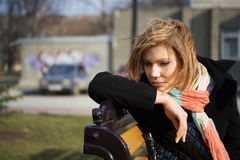 Sad young fashion woman sitting on the bench. Sad young blond fashion woman sitting on the bench Royalty Free Stock Images