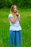 Sad young woman blowing on dandelion in hands Stock Images
