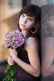 Sad young woman with chrysanthemums Royalty Free Stock Photos