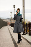 Sad young woman in classic coat with a handbag Royalty Free Stock Photos