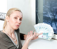 The sad young woman counts money for window repair with the burst, broken glass Stock Image