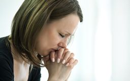 Crying woman. Sad young woman crossed  fingers  for her  face in crisis moment Royalty Free Stock Photo